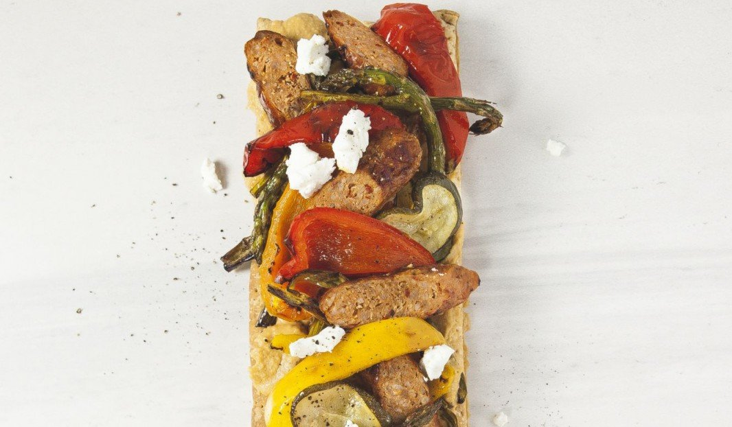 Puff pastry tart with hummus, vegetables, Italian sausage and  fresh goat cheese
